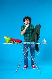 Widok z przodu młody mężczyzna trzymający zieloną koszulę na niebieskim tle czysta pralka prace domowe kolor ludzki