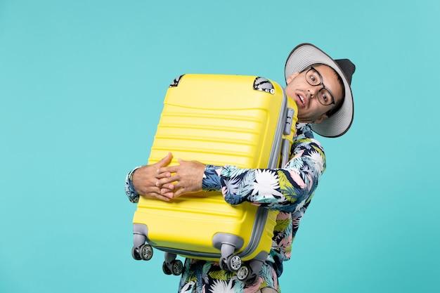 Widok z przodu młody mężczyzna udaje się na wakacje i trzyma torbę na jasnoniebieskiej przestrzeni