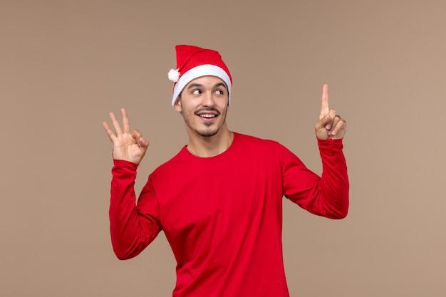 Widok z przodu młody mężczyzna uśmiecha się na brązowym tle świątecznych emocji świątecznych