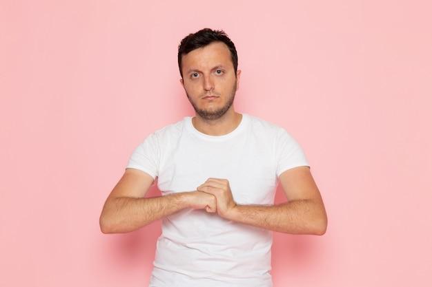 Widok z przodu młody mężczyzna w białej koszulce i dżinsach pozowanie w agresywny sposób na różowym biurku pozie emocji koloru człowieka