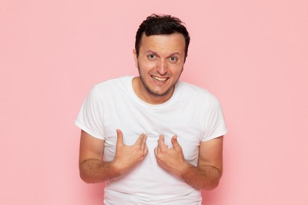 Widok z przodu młody mężczyzna w białej koszulce i dżinsach, śmiejąc się na różowym biurku pozie emocji człowieka