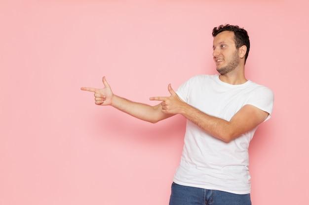 Widok z przodu młody mężczyzna w białej koszulce i niebieskich dżinsach pozowanie i uśmiechając się na różowym biurku poza kolor emocji człowieka