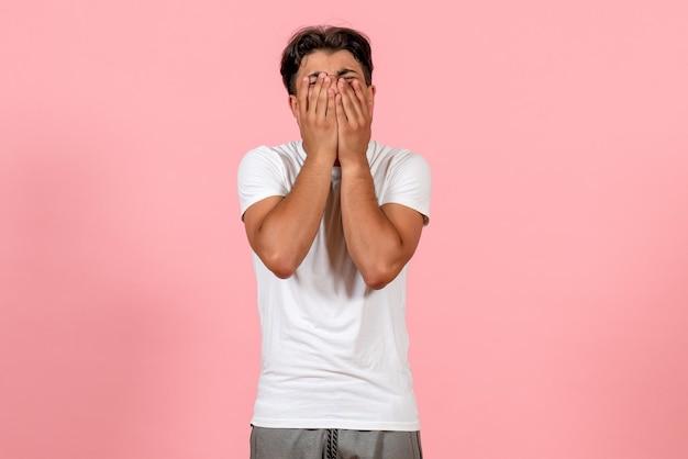 Widok z przodu młody mężczyzna w białej koszulce na różowym tle