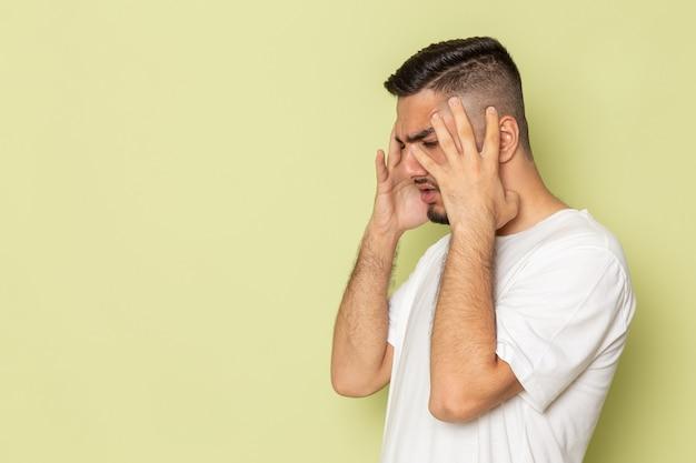 Widok z przodu młody mężczyzna w białej koszulce o bólu głowy