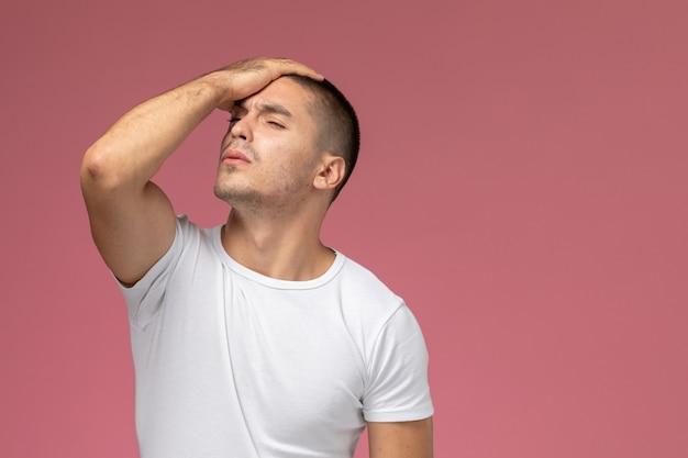 Widok z przodu młody mężczyzna w białej koszulce podkreślił i trzymał głowę na różowym tle