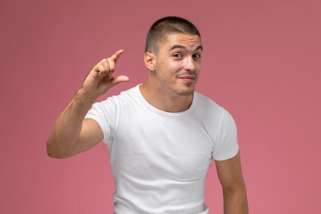 Widok z przodu młody mężczyzna w białej koszulce pokazujący rozmiar palcami na różowym tle