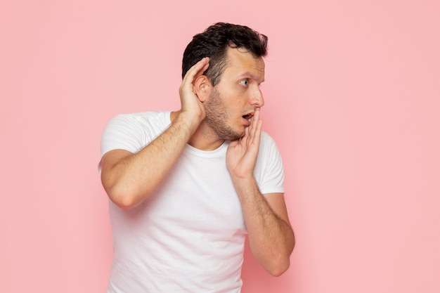 Widok z przodu młody mężczyzna w białej koszulce próbuje usłyszeć na różowym biurku pozie emocji człowieka