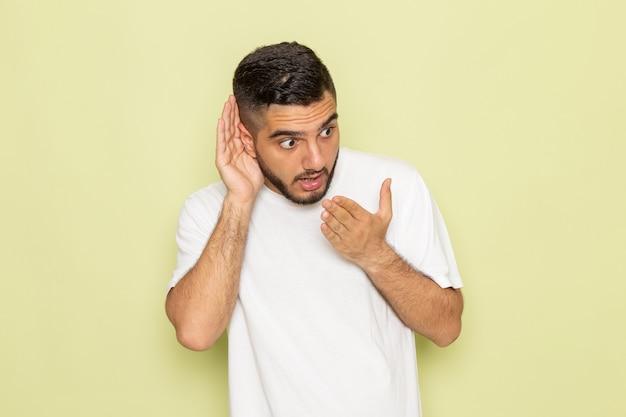 Widok z przodu młody mężczyzna w białej koszulce próbuje usłyszeć