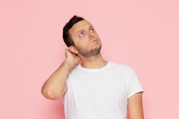 Widok z przodu młody mężczyzna w białej koszulce stwarzających z myśleniem wypowiedzi