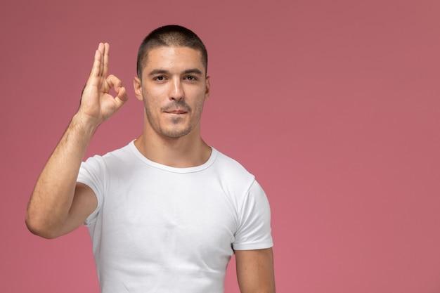 Widok z przodu młody mężczyzna w białej koszulce z podniesioną ręką na różowym tle