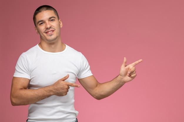 Widok z przodu młody mężczyzna w białej koszulce z uśmiechem, wskazując na różowym tle