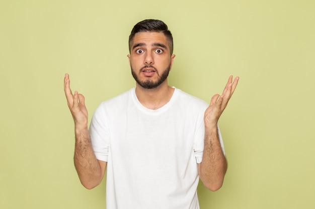 Widok z przodu młody mężczyzna w białej koszulce z zaskoczonym wyrazem