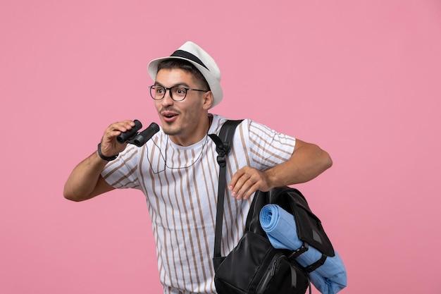 Widok z przodu młody mężczyzna w białej koszulce za pomocą lornetki na różowym tle
