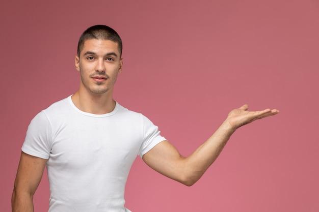 Widok z przodu młody mężczyzna w białej koszuli pozowanie z ręką na różowym tle
