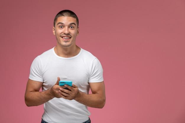 Widok z przodu młody mężczyzna w białej koszuli przy użyciu swojego telefonu i uśmiechając się na różowym tle