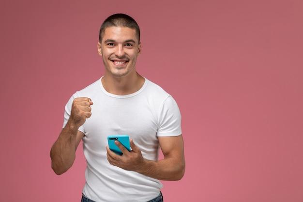 Widok z przodu młody mężczyzna w białej koszuli przy użyciu swojego telefonu z zachwyconym wyrazem twarzy na różowym tle