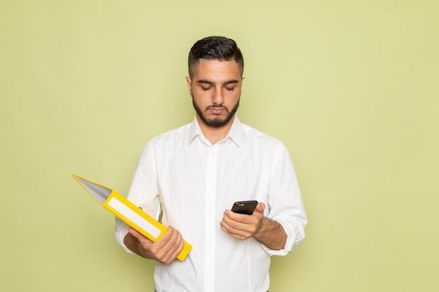 Widok z przodu młody mężczyzna w białej koszuli, trzymając żółte pliki i używając swojego telefonu