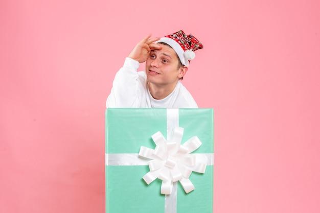 Widok z przodu młody mężczyzna w białej koszuli z prezentem na różowym tle