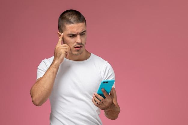 Widok z przodu młody mężczyzna w białej koszuli za pomocą swojego telefonu na różowym tle