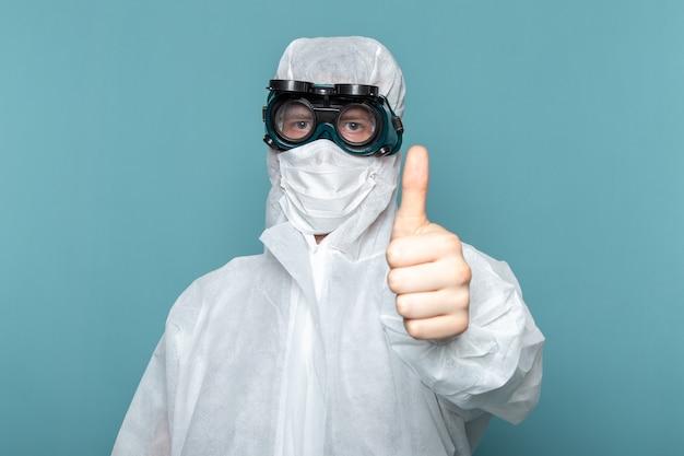 Widok z przodu młody mężczyzna w białym specjalnym garniturze i unikalnych ochronnych okularach przeciwsłonecznych na niebieskiej ścianie garnituru niebezpiecznego specjalnego koloru wyposażenia