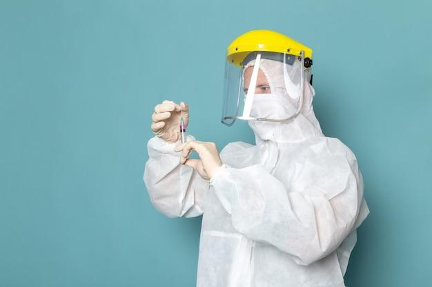 Widok z przodu młody mężczyzna w białym specjalnym garniturze i żółtym specjalnym kasku, trzymając zastrzyk na niebieskiej ścianie, mężczyzna garnitur niebezpieczeństwo specjalnego koloru sprzętu