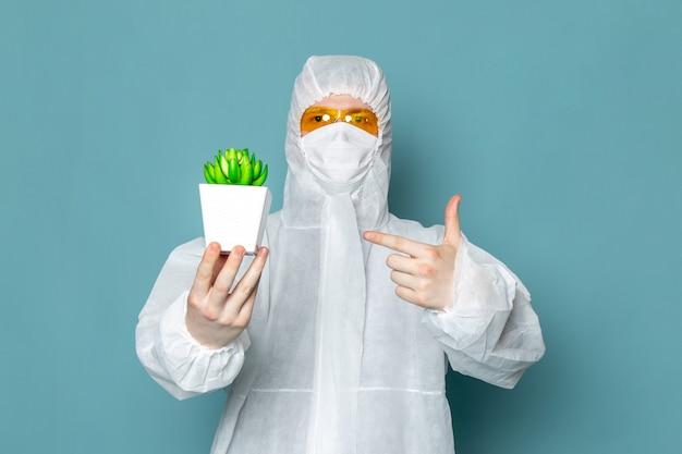 Widok z przodu młody mężczyzna w białym specjalnym garniturze, trzymając zieloną roślinę na niebieskiej ścianie