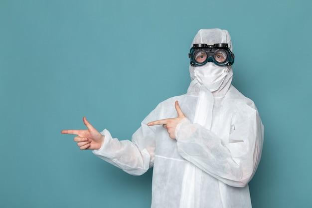 Widok z przodu młody mężczyzna w białym specjalnym garniturze, ubrany w specjalne okulary przeciwsłoneczne na niebieskiej ścianie, mężczyzna w kolorze niebezpiecznego wyposażenia specjalnego