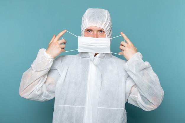 Widok z przodu młody mężczyzna w białym specjalnym garniturze, ubrany w sterylną maskę ochronną na niebieskiej ścianie, mężczyzna w kolorze zagrożenia specjalnego wyposażenia