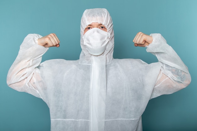 Widok z przodu młody mężczyzna w białym specjalnym garniturze, ubrany w sterylną maskę ochronną zginający się na niebieskiej ścianie