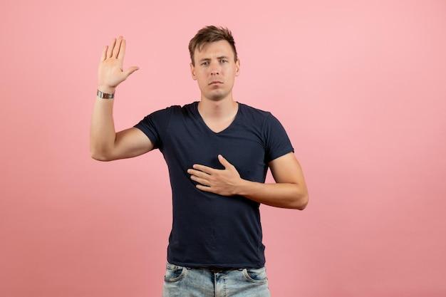 Widok z przodu młody mężczyzna w ciemnej koszulce i dżinsach pokazujący rękę na różowym tle
