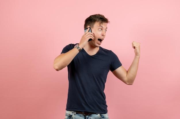 Widok z przodu młody mężczyzna w ciemnej koszulce i dżinsach rozmawia przez telefon na różowym tle