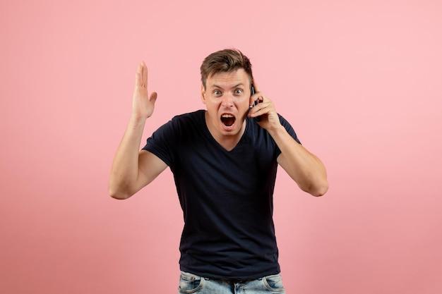 Widok z przodu młody mężczyzna w ciemnej koszulce rozmawia przez telefon na różowym tle