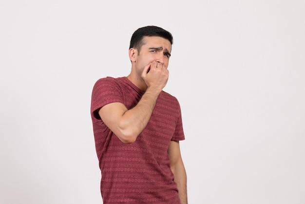 Widok z przodu młody mężczyzna w ciemnoczerwonej koszulce pozuje z przerażonym wyrazem twarzy na białym tle