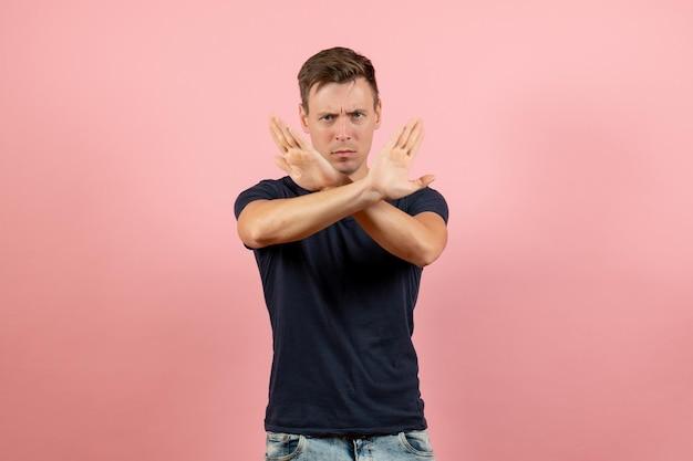 Widok z przodu młody mężczyzna w ciemnoniebieskiej koszuli pokazujący znak zakazu na różowym tle