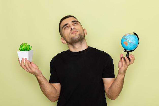 Widok z przodu młody mężczyzna w czarnej koszulce trzymający małą zieloną roślinę i małą kulę ziemską, myśląc na zielono