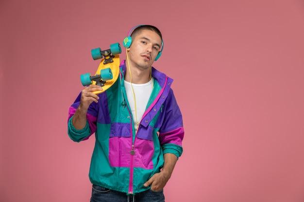 Widok z przodu młody mężczyzna w kolorowym płaszczu, słuchając muzyki trzymając deskorolkę na różowym biurku