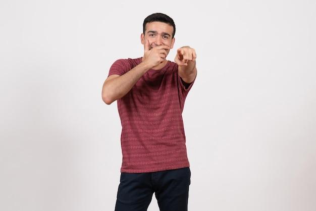 Widok z przodu młody mężczyzna w koszulce pozuje i śmieje się na białym tle