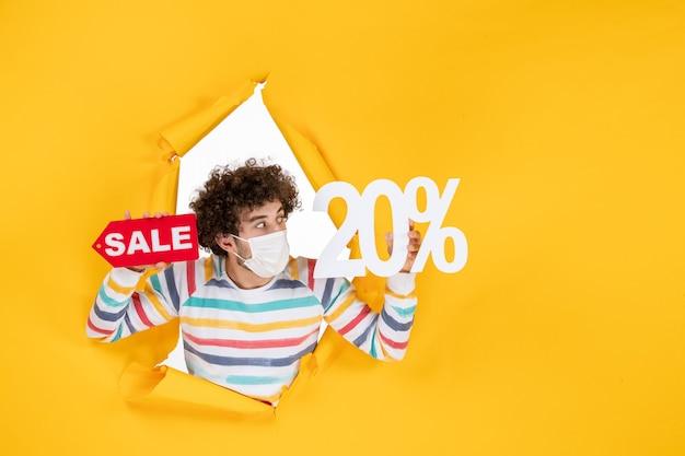 Widok z przodu młody mężczyzna w masce trzymającej i piszącej sprzedaż na żółtej sprzedaży koronawirus zdrowie covid- kolorowa pandemia zdjęć