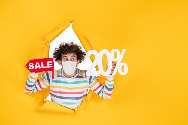 Widok z przodu młody mężczyzna w masce trzymającej i piszącej sprzedaż na żółtym kolorze zakupy koronawirus zdrowie covid- pandemia zdjęć