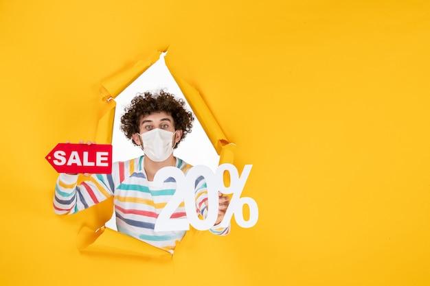 Widok z przodu młody mężczyzna w masce trzymającej i piszącej sprzedaż na żółtym kolorze zakupy zdrowie covid - pandemia zdjęć