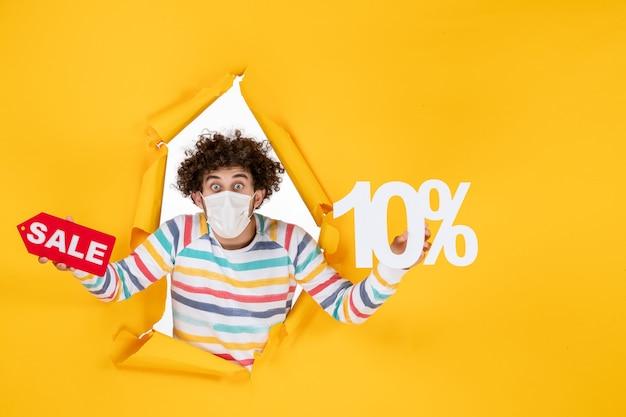 Widok z przodu młody mężczyzna w masce trzymającej i piszącej sprzedaż na żółtym zdjęciu zdrowie covid- pandemiczny kolor wyprzedaży koronawirusa
