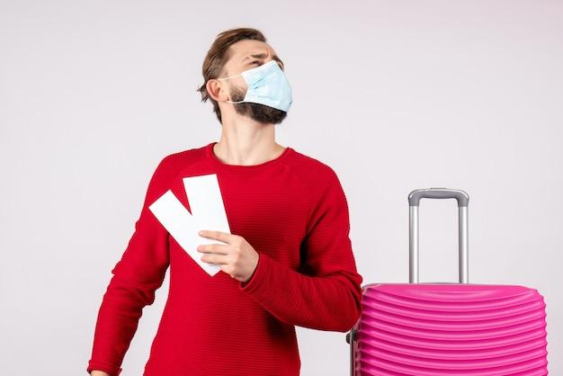 Widok z przodu młody mężczyzna w masce trzymający bilety na białej ścianie podróż covid - podróż samolotem wakacje wirus kolor emocji