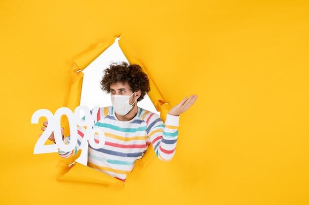 Widok Z Przodu Młody Mężczyzna W Masce Trzymający Pisanie Na żółtym Koronawirusie Pandemiczny Stan Zdrowia Covid-wyprzedaż Kolorowe Zdjęcia Darmowe Zdjęcia