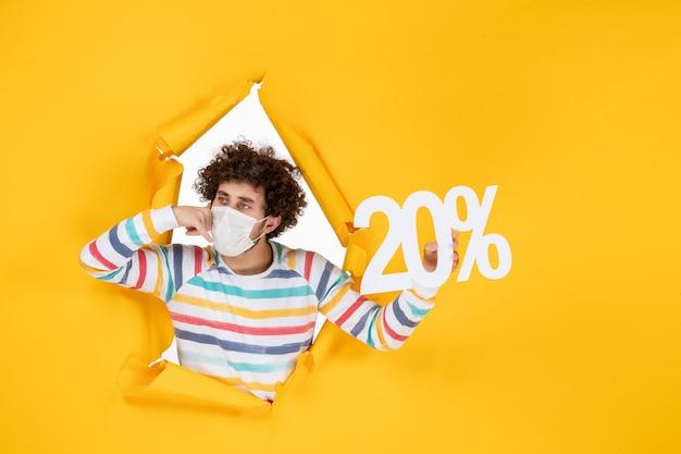 Widok z przodu młody mężczyzna w masce trzymający pisanie na żółtym pandemicznym zdrowiu covid-wyprzedaż kolorowe zdjęcie