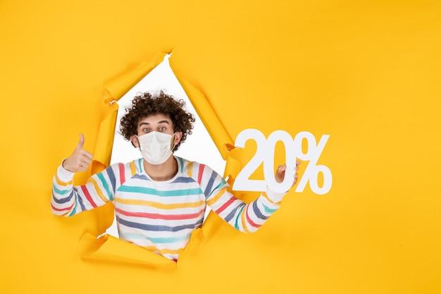 Widok z przodu młody mężczyzna w masce trzymający pisanie na żółtym pandemii pandemii koronawirusa - kolorowe zdjęcie