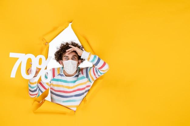 Widok z przodu młody mężczyzna w masce trzymający pisanie na żółtym wyprzedaży kolorowy wirus covid- zdjęcia zdrowie pandemiczne zakupy