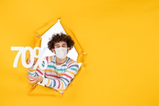 Widok z przodu młody mężczyzna w masce trzymający pisanie na żółtym wyprzedaży wirus koloru covid- zdjęcia zakupy