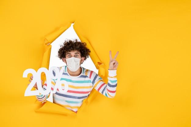 Widok z przodu młody mężczyzna w masce trzymający pisanie na żółtym zdjęciu pandemicznym koronawirusa covid - kolor sprzedaży