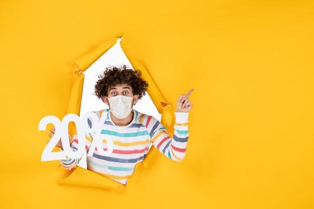 Widok z przodu młody mężczyzna w masce trzymający pisanie na żółtym zdjęciu pandemicznym koronawirusa zdrowie covid-wyprzedaż kolor