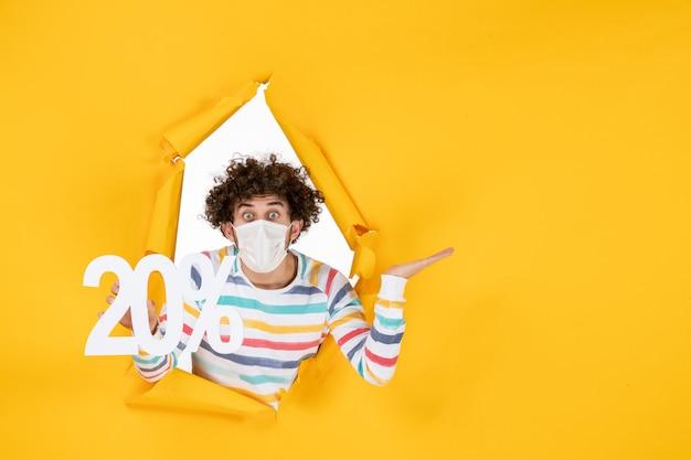 Widok z przodu młody mężczyzna w masce trzymający żółtą pandemiczną fotografię zdrowia covid-wyprzedaż koloru
